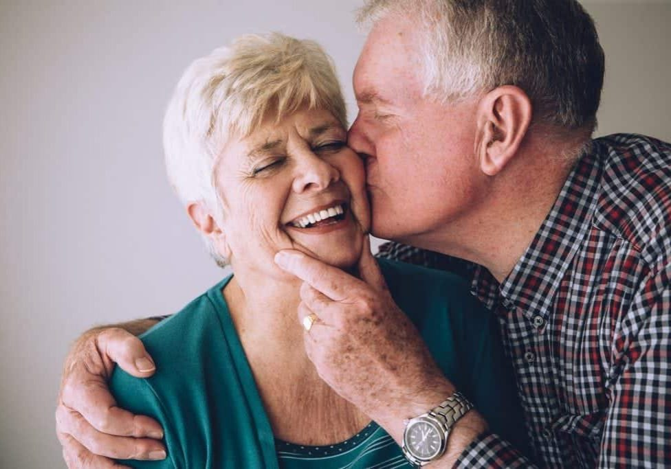 Senior man kissing his wife on the cheek. She has her eyes clsoed and is laughing.